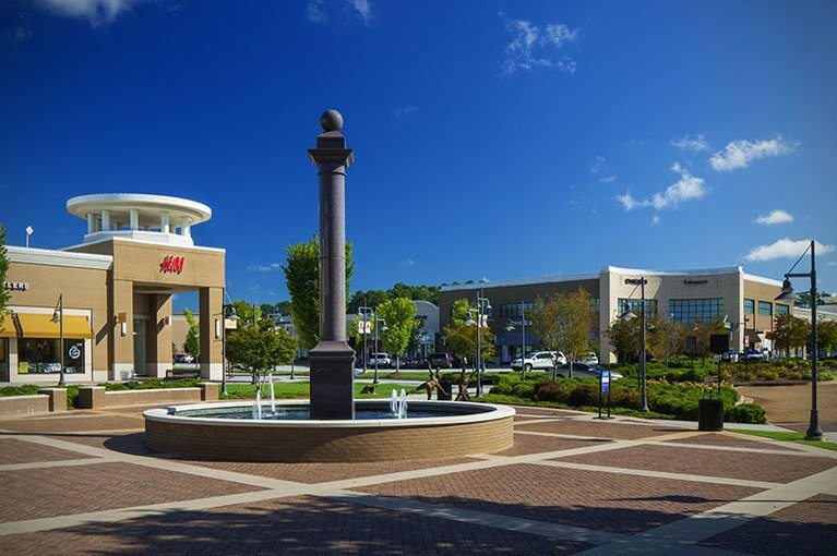 An outside common area of The Shoppes at River Crossing during the day by a running fountain where shoppers can relax.